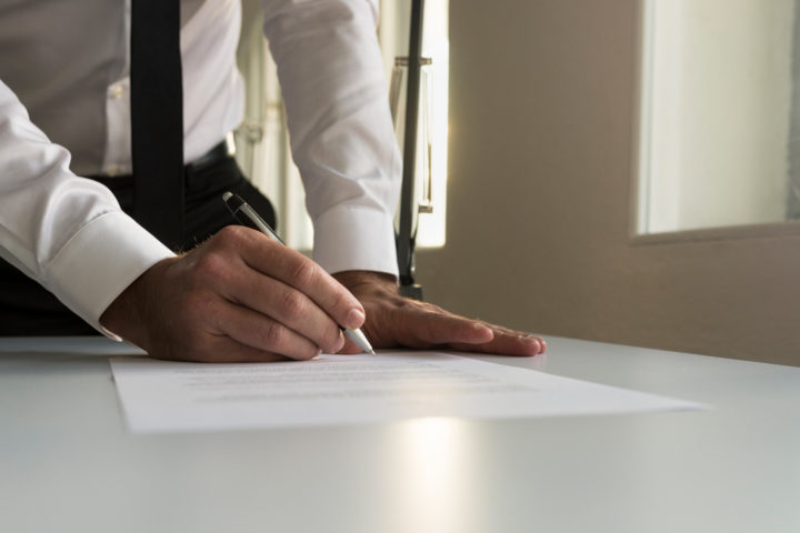 Businessman in office signing contract, document or legal papers with a natural sunlight from behind.