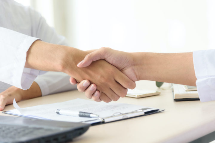 Business people shaking hands after closing deal in office, partnership merger and acquisition concept