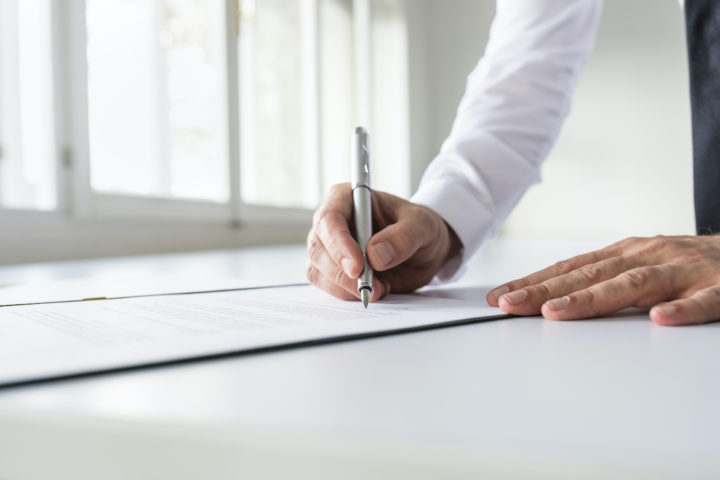 Businessman in white shirt signing contract, document or legal papers in a bright office.